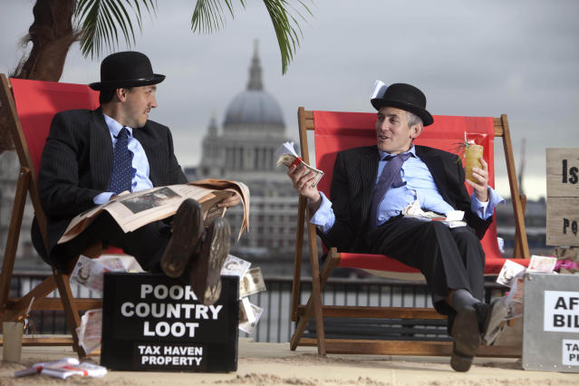 EDITORIAL USE ONLYLuke Harman (left) and Mark Webber, dressed as bankers, sit on The Isle of Shady, a pop-up tax haven set up by Enough Food for Everyone IF campaigners, sits on the South Bank of the river Thames at Gabriel's Wharf in London ahead of the Open for Growth: Tax, Trade and Transparency event on 15th June and the G8 summit. PRESS ASSOCIATION Picture date: Friday June 14, 2013. Enough Food for Everyone IF is a coalition of more than 200 organisations working together to ensure that governments tackle causes of the global hunger crisis in the year that the UK Government hosts the G8 leaders. Photo credit should read: David Parry/PA Wire