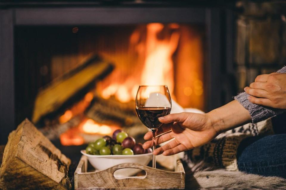 Woman in woollen socks taking a glass of red wine relaxing by the cozy fireplace