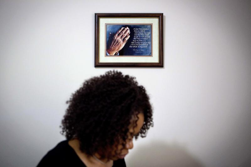 A prayer in a frame hangs on the wall as Patricia Jackson sifts through bank documents in her home Saturday, June 16, 2012, in Marietta, Ga. On a suburban cul-de-sac northwest of Atlanta, the Jacksons are struggling to keep a house worth $100,000 less than they owe. Their voices and those of many others tell the story of a country that, for all the economic turmoil of the past few years, continues to believe things will get better. But until it does, families are trying to hang on to what they've got left. The Great Recession claimed nearly 40 percent of Americans' wealth, the Federal Reserve reported last week. The new figures, showing Americans' net worth has plunged back to what it was in 1992, left economists shuddering. (AP Photo/David Goldman)