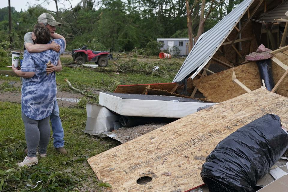 A neighbor hugs Vickie Savell next to the remains of her new mobile home early Monday, May 3, 2021, in Yazoo County, Miss. Multiple tornadoes were reported across Mississippi on Sunday, causing some damage but no immediate word of injuries. (AP Photo/Rogelio V. Solis)