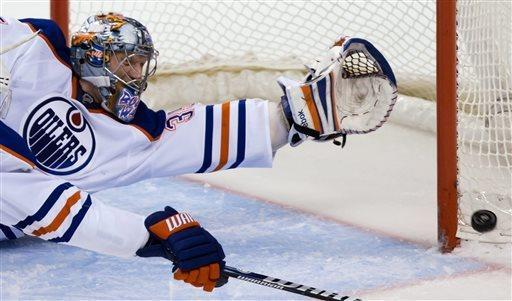 Edmonton Oilers' goalie Nikolai Khabibulin, of Russia, allows a goal to Vancouver Canucks' Henrik Sedin during the second period of an NHL hockey game Thursday, April 4, 2013, in Vancouver, British Columbia. (AP Photo/The Canadian Press, Darryl Dyck)