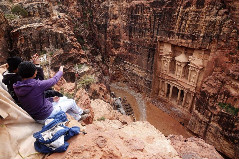 Tourists pointing to an ornate building facade carved out of red standstone.