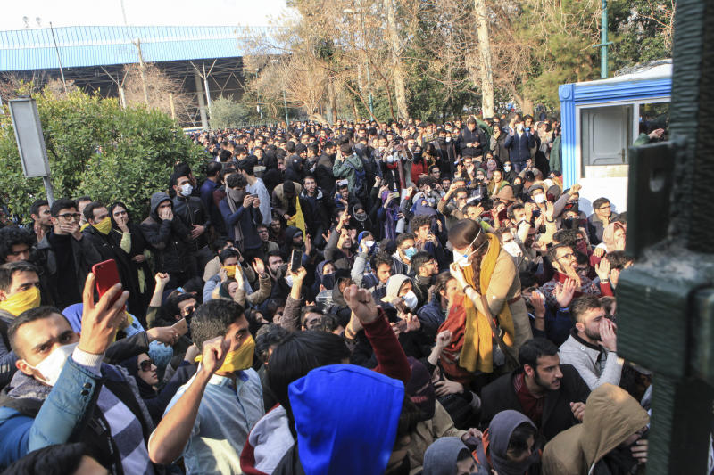 FILE - In this Dec. 30, 2017 file photo taken by an individual not employed by the Associated Press and obtained by the AP outside Iran, university students attend a protest inside Tehran University while anti-riot Iranian police prevent them to join other protestors, in Tehran, Iran. On Tuesday, June 30, 2020, Judiciary spokesman Gholamhossein Esmaili said Iran sentenced journalist Ruhollah Zam to death. Zam whose online work helped inspire the 2017 economic protests had run a website called AmadNews that posted embarrassing videos and information about Iranian officials. He had been living and working in exile in Paris before being convinced into returning to Iran, where he was arrested in October 2019. (AP Photo, File)
