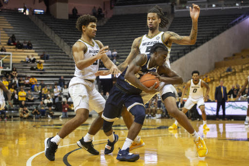 Charleston Southern's Dontrell Shuler, center, tries to dribble around Missouri's Mitchell Smith, right, and Mark Smith, left, during the second half of an NCAA college basketball game Tuesday, Dec. 3, 2019, in Columbia, Mo. Charleston Southern won the game 68-60. (AP Photo/L.G. Patterson)