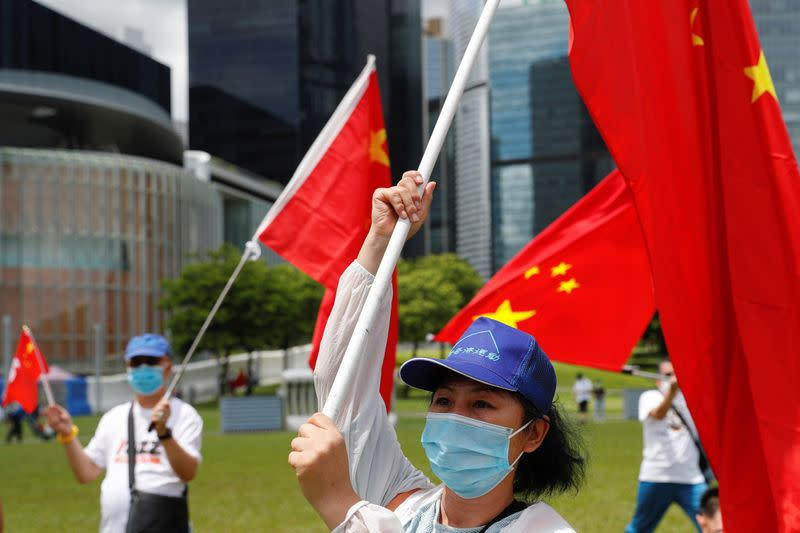 Pro-China supporters celebrate with Hong Kong and Chinese flags after China's parliament passes the national security law for Hong Kong, in Hong Kong