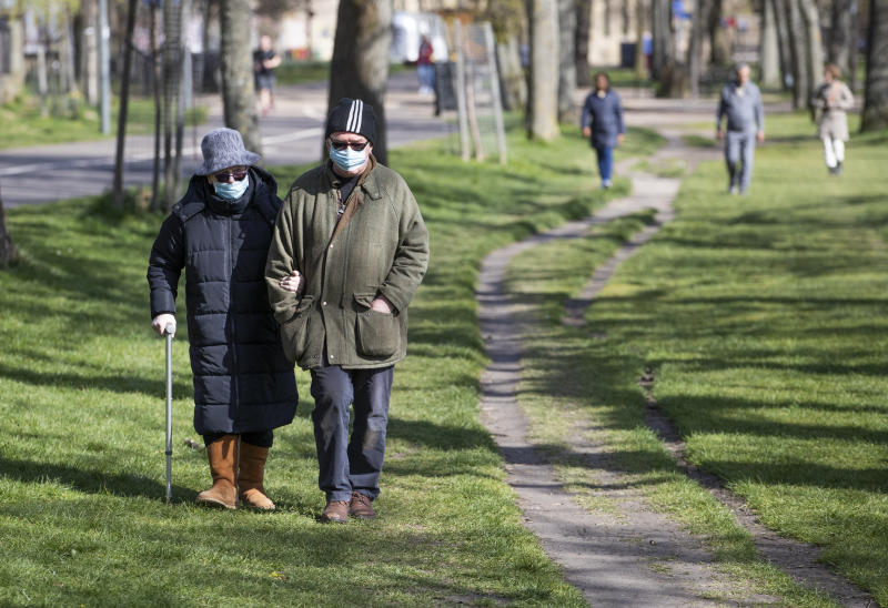 A couple wearing protective face masks walk through The Meadows, Edinburgh, during the sunny Easter bank holiday weekend, as the UK continues in lockdown to help curb the spread of the coronavirus.