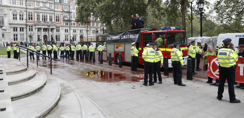 Extinction Rebellion climate activists stand on a fire engine outside the Treasury building in London, Thursday, Oct. 3, 2019. Climate activists sprayed hundreds of liters (gallons) of fake blood on the British government building, hoping to underscore the damage humans are causing to the planet. (AP Photo/Alastair Grant)