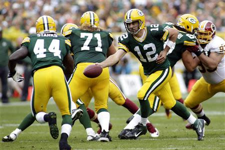 Green Bay Packers quarterback Aaron Rodgers (C) hands off the ball to running back James Starks (L) during the first half of their NFL football game against the Washington Redskins in Green Bay, Wisconsin September 15, 2013. The Packers defeated the Redskins 38-20. REUTERS/Darren Hauck