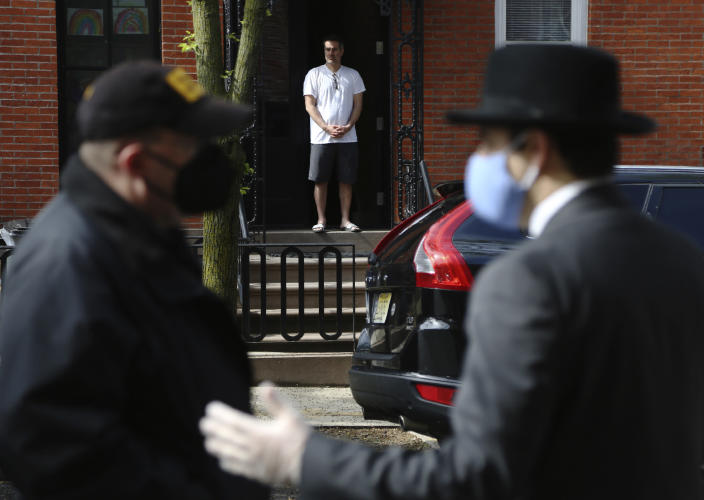 FILE - In this May 3, 2020, file photo, Paul Catanzaro stands in his doorway across the street from Scotto Funeral Home, praying alongside a small group gathered to say goodbye as the body of the Rev. Jorge Ortiz-Garay is prepared for transport in the Brooklyn borough of New York. Ortiz-Garay was the first Catholic cleric in the United States to die from the coronavirus outbreak. He was recently flown to Mexico City where his body was laid to rest. (AP Photo/Jessie Wardarski, File)