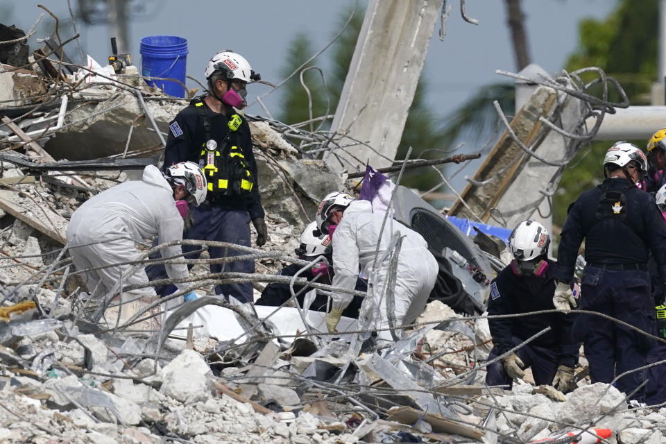 Rescue workers handle a tarp containing recovered remains at the site of the collapsed Champlain Towers South condo building on Monday. Source: AP