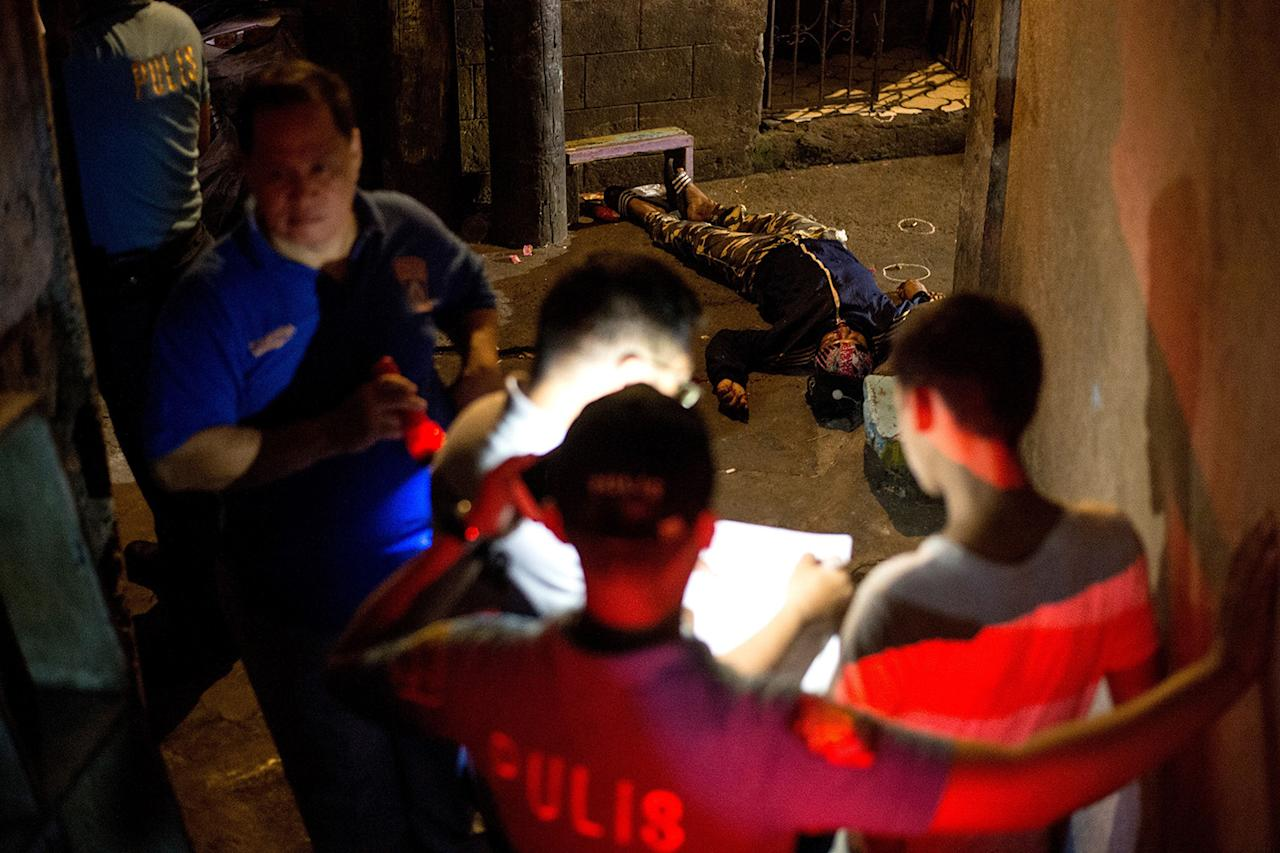 <p>Officials stanad over the body of an alleged drug dealer killed by an unidentified assailant in Manila, Philippines, March 29, 2017. (Noel Celis/AFP/Getty Images) </p>