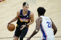 Phoenix Suns guard Devin Booker (1) looks to pass as Philadelphia 76ers center Joel Embiid (21) defends during the second half of an NBA basketball game, Saturday, Feb. 13, 2021, in Phoenix.(AP Photo/Matt York)