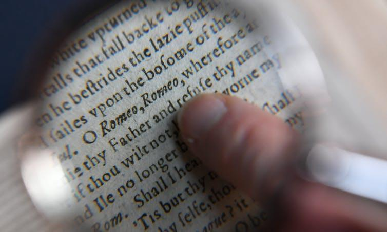 Person's finger on magnified page of Shakespeare's Romeo and Juliet, reading: