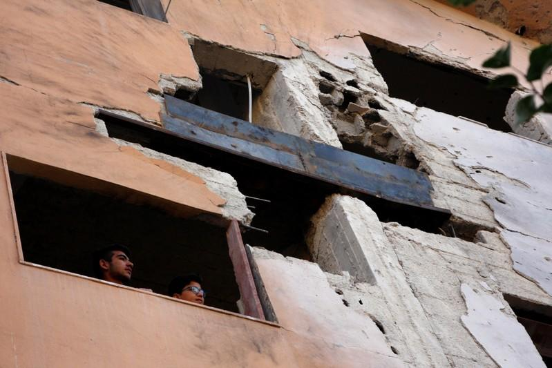 Boys look out the window of a building, damaged from an Israeli attack in Damascus