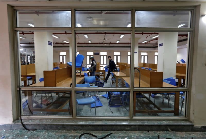 FILE PHOTO: People walk inside a partially damaged library of the Jamia Millia Islamia university in New Delhi