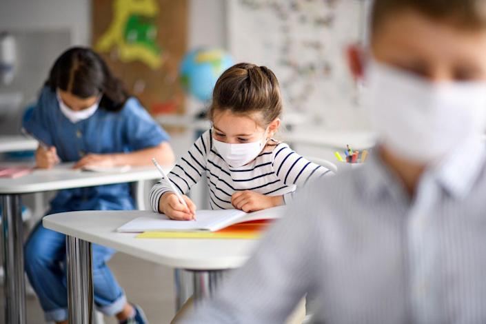 Small children with face mask back at school after covid-19