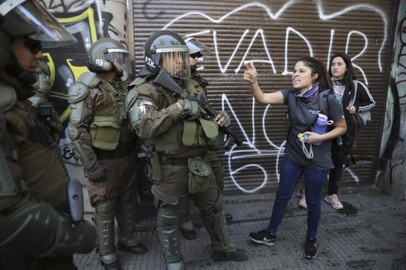 An anti-government demonstrator screams at riot police in Santiago, Chile, Tuesday, Oct. 22, 2019. Protesters defied an emergency decree and confronted police in Chile's capital continuing disturbances that have left at least 15 dead. (AP Photo/Rodrigo Abd)