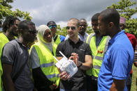 In this photo taken Thursday, Oct. 31, 2019, Eduardo Rodriguez, center, of drone manufacturer DJI, shows trainee drone pilots from the State University of Zanzibar how to fly a drone to spray the breeding grounds of malaria-carrying mosquitoes, at Cheju paddy farms in the southern Cheju region of the island of Zanzibar, Tanzania. Drones spraying a silicone-based liquid that spreads across the large expanses of stagnant water where malaria-carrying mosquitoes lay their eggs, are being tested to help fight the disease on the island of Zanzibar, off the coast of Tanzania. (AP Photo/Haroub Hussein)