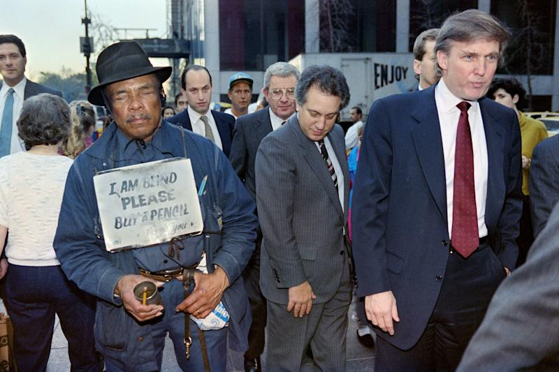 Donald Trump, far right, walks down Fifth Avenue in New York past a beggar after holding a news conference on Nov. 16, 1990. Trump announced he had reached a deal that will temporarily put his Taj Mahal casino into bankruptcy protection.