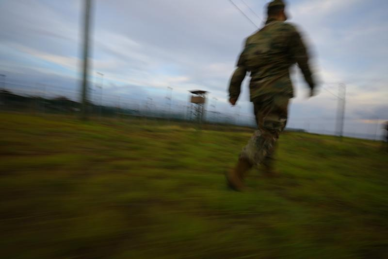 "An unidentified member of the U.S. Army walks by an empty prison camp at the U.S. Naval Base in Guantanamo Bay, Cuba, June 4, 2017. REUTERS/Carlos Barria SEARCH ""GUANTANAMO COMBO"" FOR THIS STORY. SEARCH ""WIDER IMAGE"" FOR ALL STORIES."