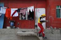 """Circus clown Julio Cesar Chiroque, 38, whose clown name is """"Galleta,"""" or Cookie, leaves a residence where he failed to sell candied apples as he makes the rounds in a poor neighborhood on the outskirts of Lima, Peru, Wednesday, Aug. 5, 2020. Chiroque's family used to run their own small circus, but since March when the lockdown to curb COVID-19 closed their business, and the requirement for seniors over 60 to self-quarantine kept his father home-bound, they started selling circus food to survive. (AP Photo/Martin Mejia)"""