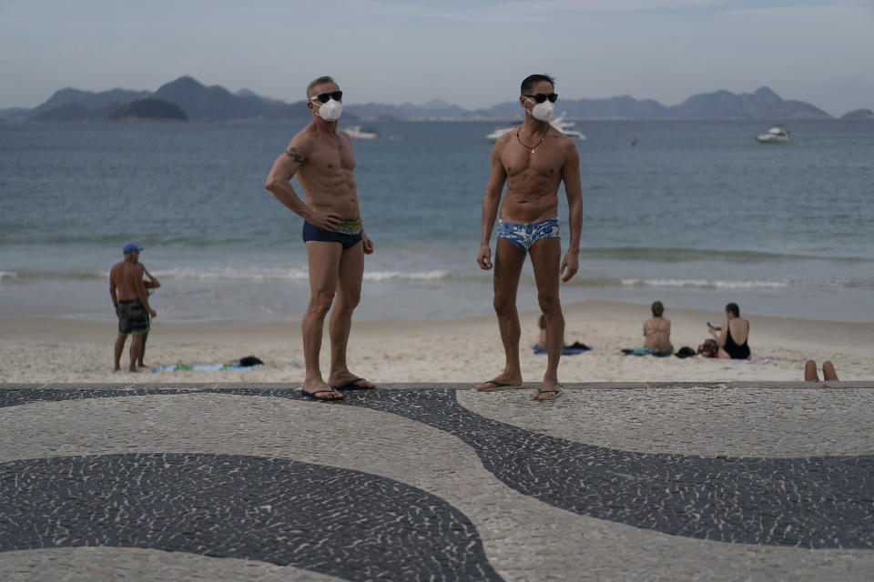 """Jesus Costa and Antonio Ancon, right, stand on Copacabana beach amid the outbreak of the new coronavirus in Rio de Janeiro, Brazil, Sunday, July 12, 2020. """"I prefer to have tan lines on the face than to put my life at risk"""" says Ancon about the use of the face masks at the beach as a measure to curb the spread of the new coronavirus. (AP Photo/Leo Correa)"""