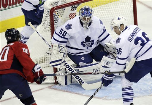 Toronto Maple Leafs goalie Jonas Gustavsson (50) eyes and block a shot off the sick of Washington Capitals center Marcus Johansson (90) as Maple Leafs defenseman Carl Gunnarsson (36) helps defend during the first period of an NHL hockey game on Sunday, March 11, 2012, in Washington. (AP Photo/Carolyn Kaster)