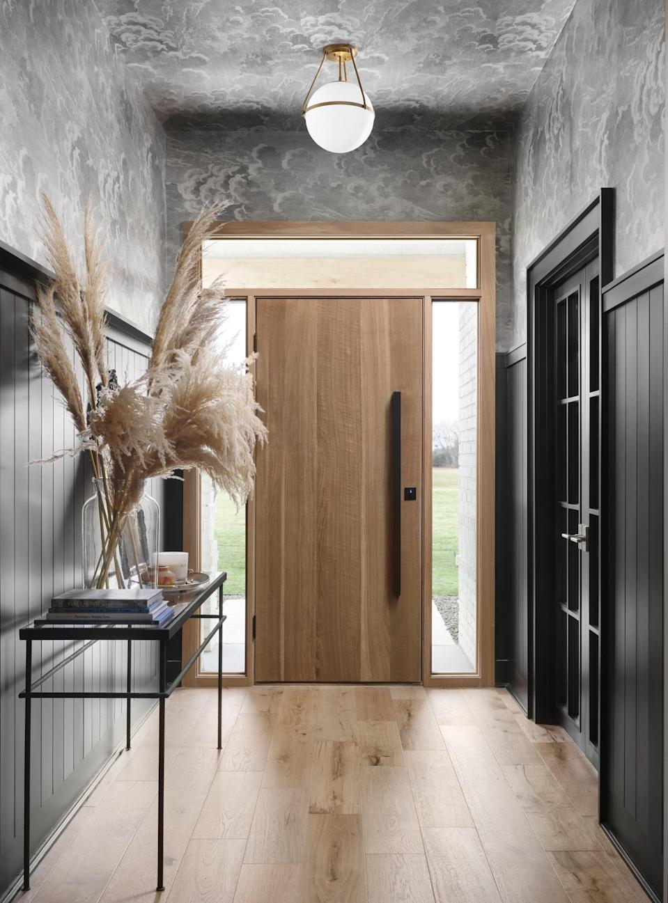 <p>Chip and Joanna turned a lackluster entry into a dramatic one filled with black panelling and fully wallpapered walls and ceilings. To accentuate the moody mid-century vibe, Chip and Joanna installed a window-framed white oak door and a brass-detailed light fixture.</p>