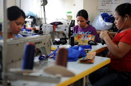 Workers sew recycled materials into handbags at the Philippine Christian Foundation building in Manila on June 13. Jane Walker teaches women to make purses and jewellery using items discarded by the public - from candy wrappers to drink cans