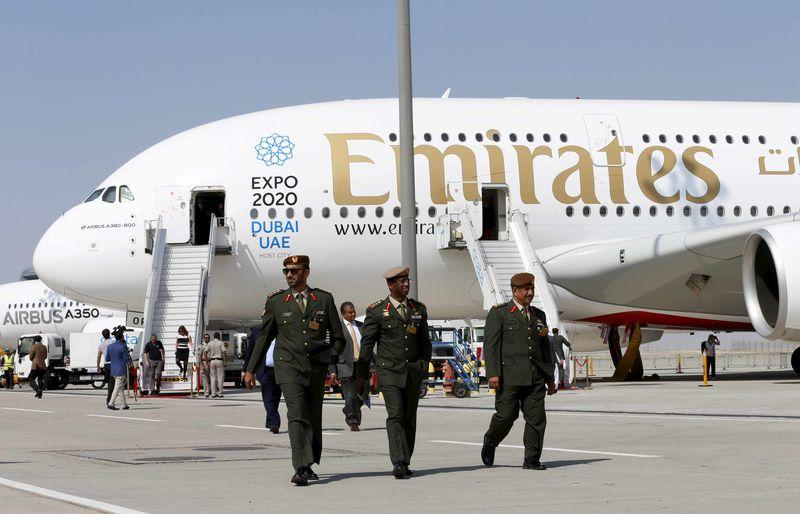 UAE officers walk in front of Emirates Airbus A380 plane at the Dubai Airshow