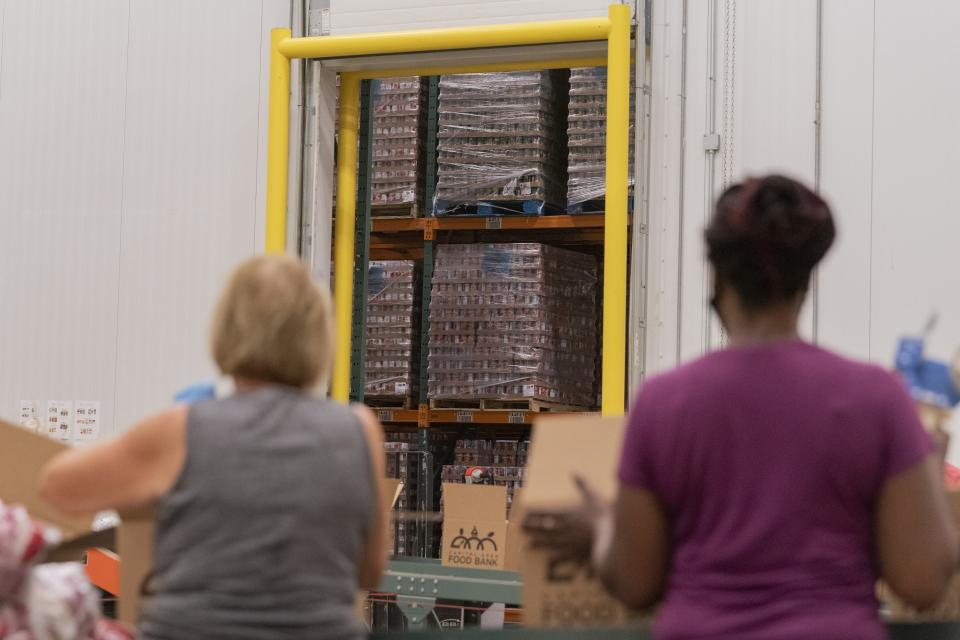 With the warehouse of food items seen through the warehouse door, volunteers pack boxes of food at The Capital Area Food Bank, Tuesday, Oct. 5, 2021, in Washington. (AP Photo/Jacquelyn Martin)