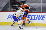 Philadelphia Flyers' Nolan Patrick, right, is checked into the boards by Buffalo Sabres' Tobias Rieder during the first period of an NHL hockey game, Monday, Jan. 18, 2021, in Philadelphia. (AP Photo/Derik Hamilton)