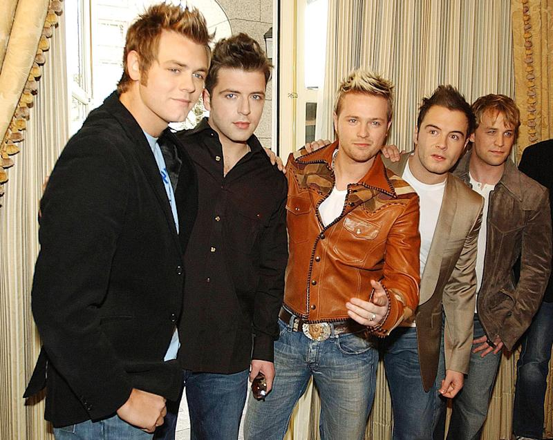 Bryan McFadden, left, poses with the remaining members of Westlife, starting second from left, Mark Feehily, Nicky Byrne, Shane Filan and Kian Egan, after announcing his departure from the group during a press conference in Dublin Tuesday March 9, 2004. The four remaining band members have vowed to press on without McFadden, but some believe his announcement could mark the end for the band. (AP Photo/John Cogill)