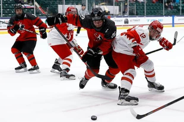 Mason McTavish, centre, battles for the puck against Dmitri Katelevski of Russia during the 2021 IIHF Ice Hockey U18 World Championship in Texas. McTavish is one of two Ottawa-area players to be picked early in the 2021 NHL draft. (Tom Pennington/Getty Images - image credit)