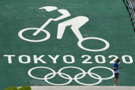 A worker looks at the start ramp at the BMX racing track as preparations continue for the 2020 Summer Olympics, Tuesday, July 20, 2021, at the Ariake Urban Sports Park in Tokyo. (AP Photo/Charlie Riedel)
