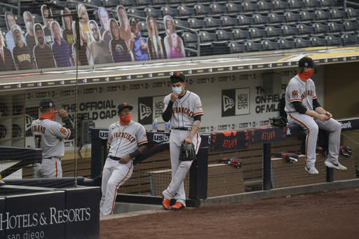San Francisco Giants wear masks after hearing their baseball game against the San Diego Padres had been postponed, Friday, Sept. 11, 2020, in San Diego, minutes before the scheduled first pitch. No reason was immediately given. (AP Photo/Gregory Bull)