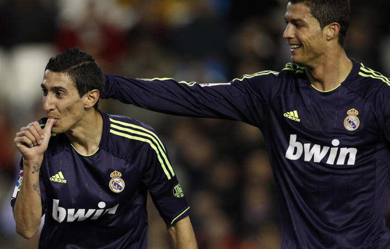 Real Madrid's Angel Di Maria from Argentina, left, is congratulated by teammate Cristiano Ronaldo from Portugal after scoring a goal against Valencia during their La Liga soccer match at the Mestalla stadium in Valencia, Spain, Sunday, Jan. 20, 2013. (AP Photo/Alberto Saiz)