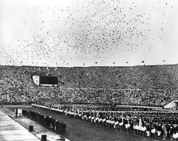 """<p>Distance runner Paavo Nurmi and Hannes Kolehmainen, known as """"The Flying Finns,"""" light two seperate cauldrons. Thousands of carrier pigeons are released to start the Games.</p>"""