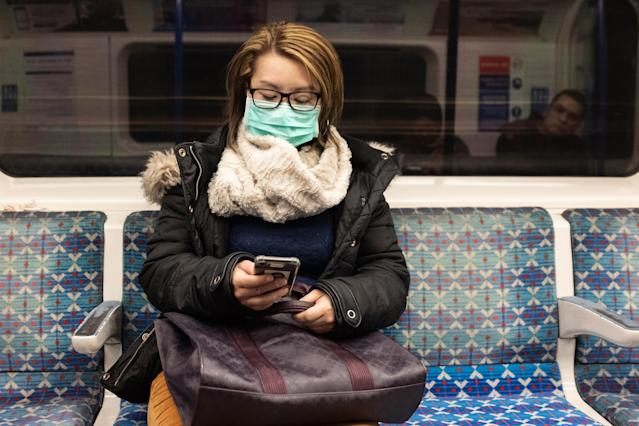 A passenger is pictured wearing a mask on the London Underground on 26 February. The UK has 13 confirmed cases. (Getty Images)