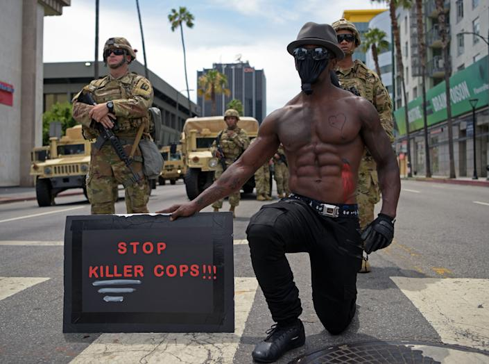 """<i>A protester kneels as he holds a placard that says """"Stop killer cops!!!!"""" in front of a row of Army National Guard troops during a June 2 demonstration in Hollywood, California.</i>"""