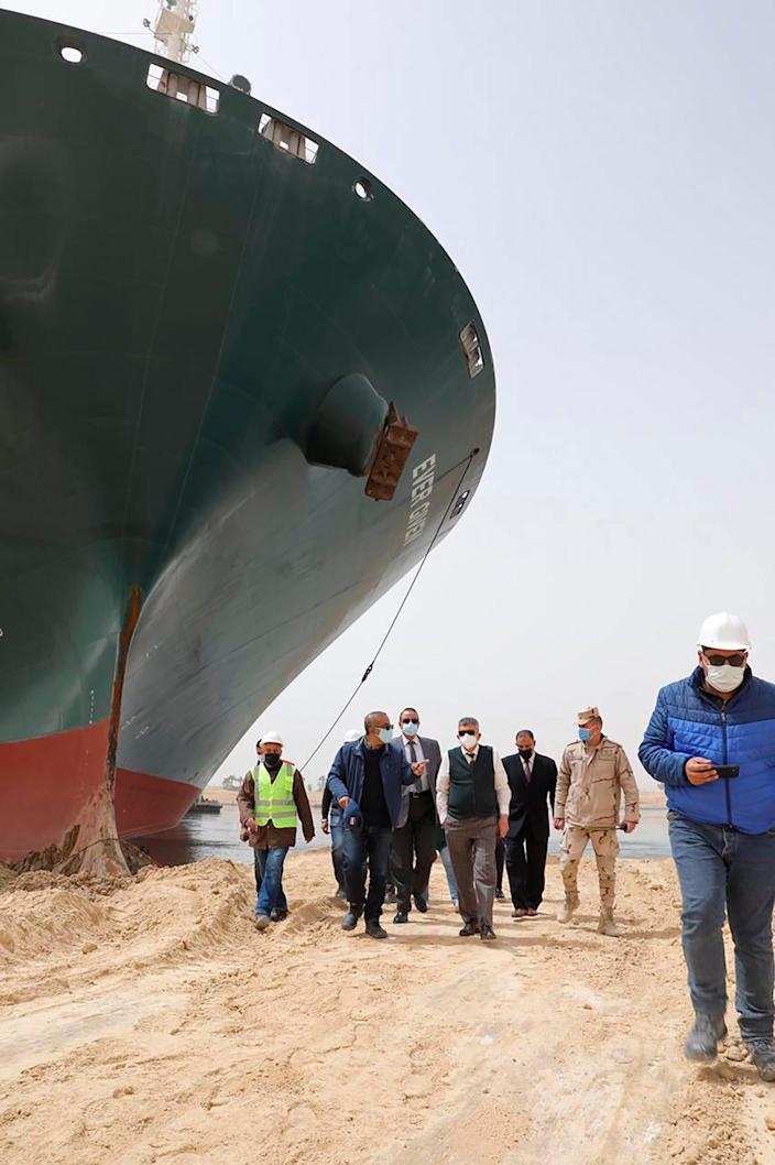 This photo released by the Suez Canal Authority on March 25, 2021, shows Lt. Gen. Ossama Rabei, center, head of the Suez Canal Authority, with a team walking along the bank of the Suez Canal where the Ever Given, a Panama-flagged cargo ship, has become wedged across the Suez Canal and blocking traffic in the vital waterway.