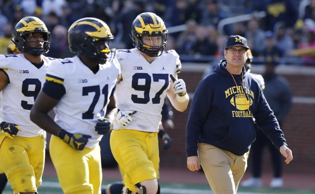 Michigan head coach Jim Harbaugh walks out with players during the team's annual spring NCAA college football game, Saturday, April 13, 2019, in Ann Arbor, Mich. (AP Photo/Carlos Osorio)