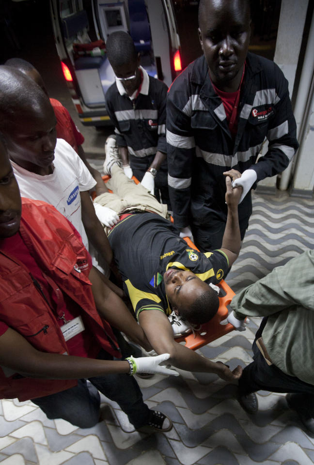 A man injured in a grenade attack at a downtown bus station has his hand held by a paramedic as he is carried from an ambulance at Kenyatta Hospital in Nairobi, Kenya Saturday, March 10, 2012. Explosions at one of the Kenyan capital's main bus terminals killed at least two people and left two dozen others wounded Saturday, officials and witnesses said. (AP Photo/Ben Curtis)