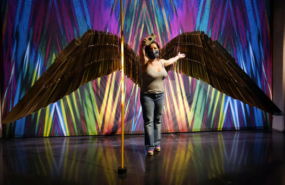 """Dawn Garcia takes a selfie in front of Golden Armor Wings featured in the film """"Wonder Woman 1984"""" in the """"Action and Magic Made Here"""" interactive experience at the Warner Bros. Studio Tour Hollywood media preview on June 24, 2021, in Burbank, Calif. (AP Photo/Chris Pizzello)"""