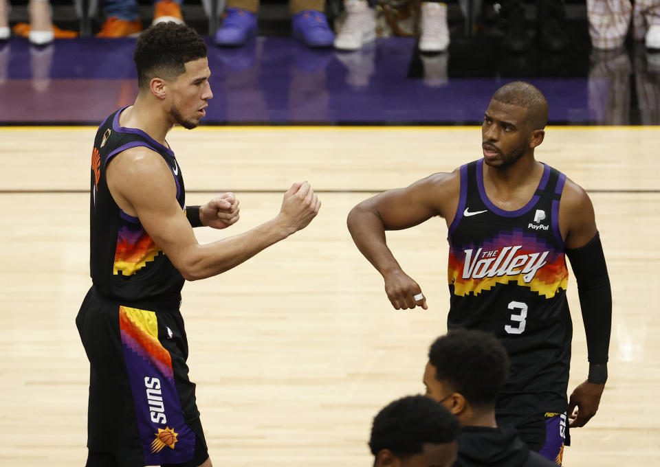 PHOENIX, ARIZONA - JULY 08: Devin Booker #1 of the Phoenix Suns celebrates with Chris Paul #3 against the Milwaukee Bucks during the first half in Game Two of the NBA Finals at Phoenix Suns Arena on July 08, 2021 in Phoenix, Arizona. NOTE TO USER: User expressly acknowledges and agrees that, by downloading and or using this photograph, User is consenting to the terms and conditions of the Getty Images License Agreement. (Photo by Christian Petersen/Getty Images)