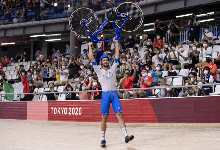 <p>IZU, JAPAN - AUGUST 04: Filippo Ganna of Team Italy lifts his bike to celebrates winning a gold medal after setting a new World record during the Men's team pursuit finals, gold medal of the track cycling on day twelve of the Tokyo 2020 Olympic Games at Izu Velodrome on August 04, 2021 in Izu, Japan. (Photo by Justin Setterfield/Getty Images)</p>