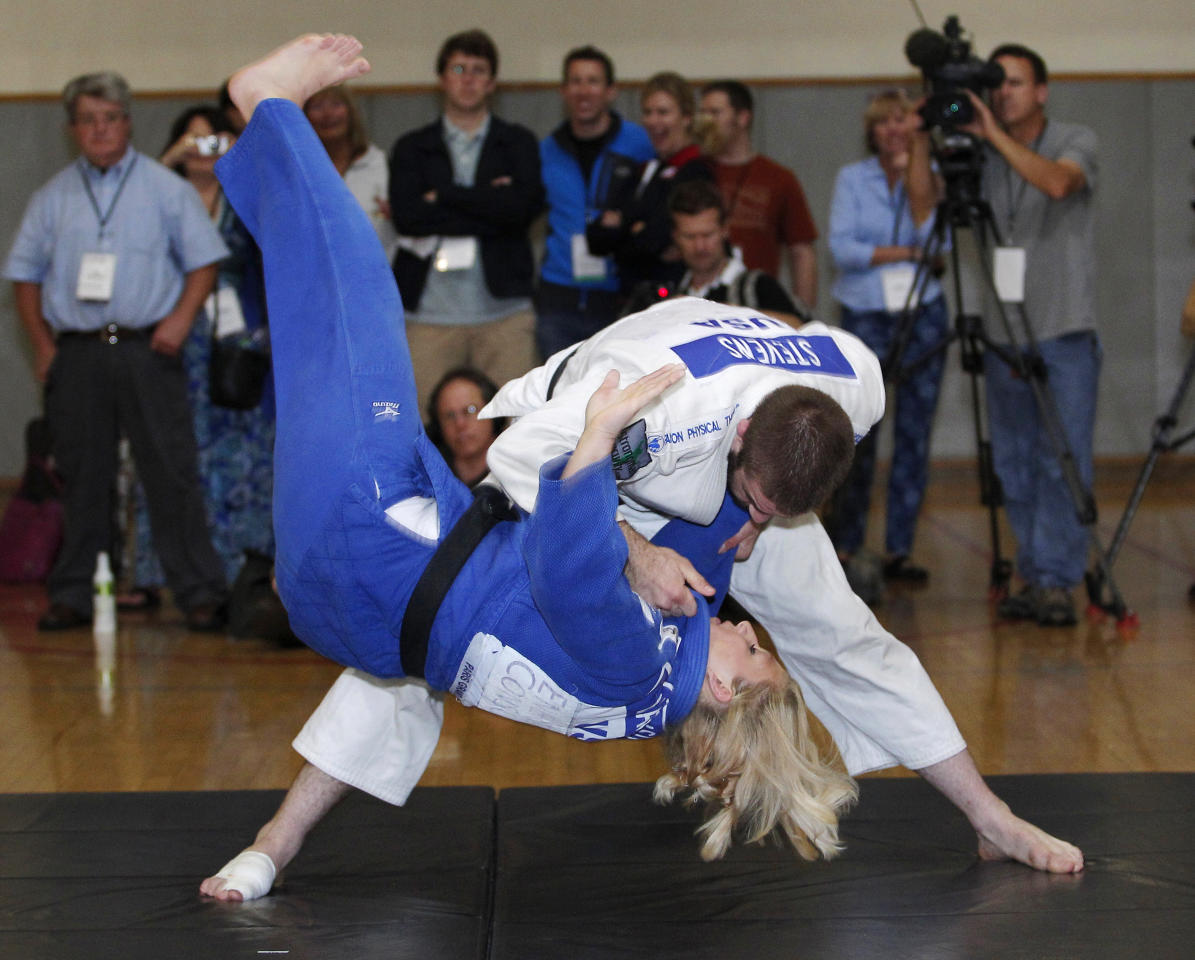 2010 world champion Kayla Harrison (L) is thrown onto the mat by 2008 Olympian Travis Stevens (R) during a judo demonstration at the U.S. Olympic Committee Media Summit in Dallas, Texas May 13, 2012.  REUTERS/Tim Sharp (UNITED STATES - Tags: SPORT OLYMPICS JUDO)