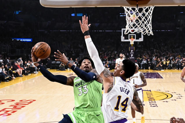 Minnesota Timberwolves' Robert Covington (33) goes to basket under pressure from Los Angeles Lakers' Danny Green (14) during the first half of an NBA basketball game, Sunday, Dec. 8, 2019, in Los Angeles. (AP Photo/Ringo H.W. Chiu)