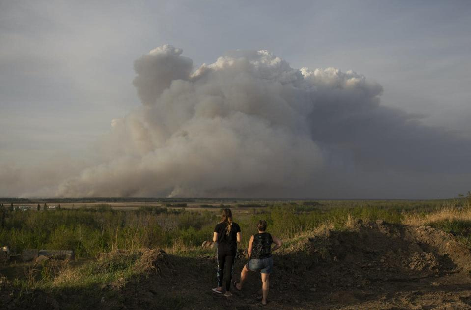 """<span class=""""caption"""">Wildfire smoke rises near Prince Albert, Sask., in May 2021, where a fast-moving wildfire led local officials to declare a state of emergency.</span> <span class=""""attribution""""><span class=""""source"""">THE CANADIAN PRESS/Kayle Neis</span></span>"""