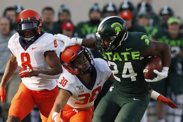 Michigan State running back Elijah Collins (24) pushes Illinois defensive back Sydney Brown (30) during the first half of an NCAA college football game, Saturday, Nov. 9, 2019, in East Lansing, Mich. (AP Photo/Carlos Osorio)